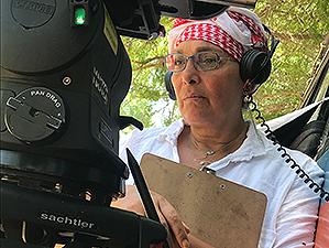 Regisseurin Manijeh Hekmat steht mit Kopfhörern auf den Ohren hinter einer Kamera.
