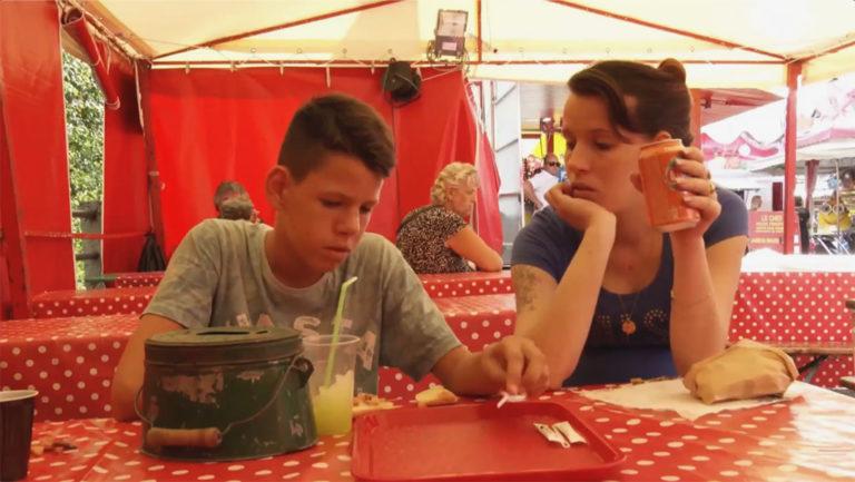Mutter und Sohn bei einem Fest im Imbisszelt