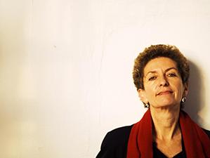 Porträt von Ruth Beckermann vor einer weißen Wand.