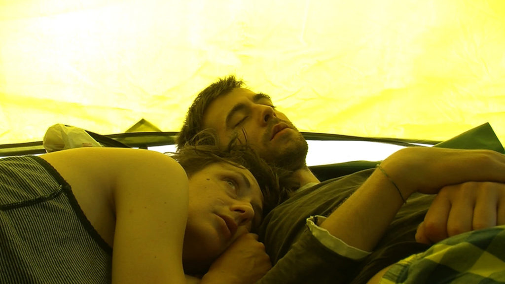Ein Paar liegt im Zelt, dessen Außenwand das Bild in gelbes Licht tönt