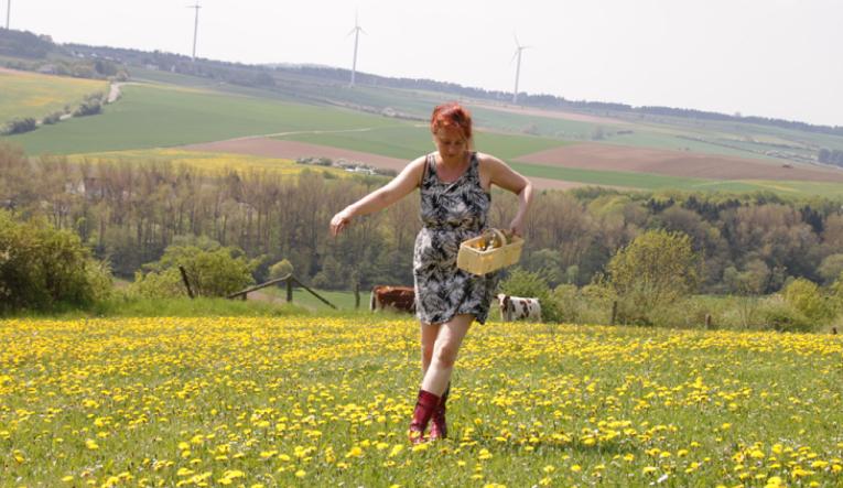 Filmemacherin Dagie Brundert trägt ein geblümtes Sommerkleid und geht über eine Wiese