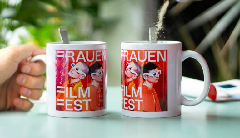 Zwei Kaffeetassen mit dem Key Visual des Festivals 2021