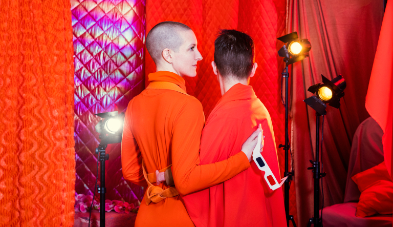 Two persons in orange clothes with the back to the camera